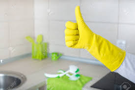 kitchen counter close up. Clean Kitchen Countertop And Furniture In Background. Conceptual Image Of Home Cleaning. Close Up Human Hand With Yellow Rubber Glove Showing Counter I