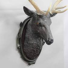 an antique black forest stag head with real antlers in livesize wooden base with plaster