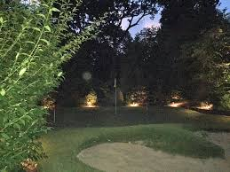 outdoor lighting at this backyard putting green allows for unlimited evening rounds of golf