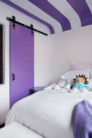 adorable girl s room features white and purple striped ceiling over full bed dressed in soft white bedding and purple throw blanket next to purple sliding