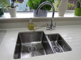 a bluci orbit 01 u undermounted 1 5 bowl kitchen sink and a twin lever bluci rienza kitchen tap set into quartz worktop with drainer grooves