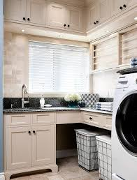 tan laundry room cabinets with black granite countertops