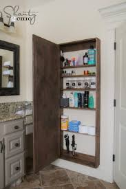 a wooden diy bathroom storage cabinet is storing listerine rubbing alcohol nail polish