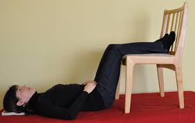 lie down with legs resting over a chair to ease back pain