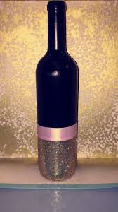 Wine Bottle that we Spray Painted Black. Before spray paint, the bottle was  green. Gold glitter and pink ribbon.