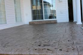 stamped concrete patio outside of kalamazoo michigan with a sliding door and concrete step