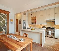 the open kitchen and dining area juxtaposes new cabinetry and tiles with red woodwork details and parquet flooring