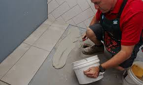 man applying adhesive before laying the tiles