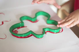 then sweet girl dipped the cookie cutters into the paint and pressed them onto the paper