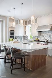 modern pendant lights over long wood kitchen island stock photo for ideas 15