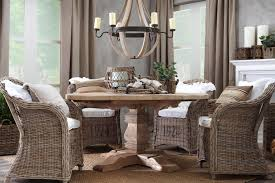 traditional round wooden dining table under decorative chandelier paired with comfortable rattan dining chairs