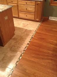 interior hardwood to tile floor transition with small mosaic tiles as the divider a kitchen set and kitchen island tile to wood floor transition ideas