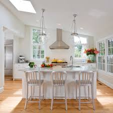 monochromatic kitchen with sloped ceiling framing skylight over white cabinets pairing with nickel hardware white counters and a subway tile backsplash