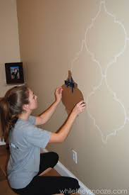 DIY Moroccan-Style Wall Stencil Tutorial - tape a level to your stencil to  get