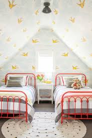 Great wallpaper choice for a child's room. Love the bright red beds, too.