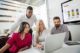 top ideas for recruiting great candidates 4 coworkers studying a checklist on a laptop