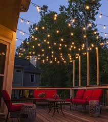 hang patio lights across a backyard deck outdoor living area or patio guide for
