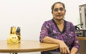 professor shoba krishnan sits at the small round table where she meets with students one