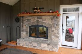 rustic outdoor wood burning fireplace with large natural stone mantle and closed hearth