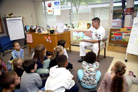 U S Navy Yeoman 1st Class Jose Wrangal Reads A Book To