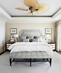 silver gray bedroom with tray ceiling and blade ceiling fan