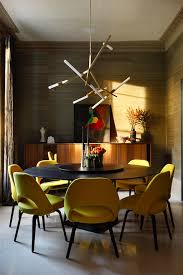 a stunning mid century modern inspired dining room with chartreuse green velvet dining chairs and round table see more inspirational rooms from the
