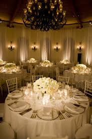 White linens and flowers, pinspot Lighting and low centerpieces create  elegance.