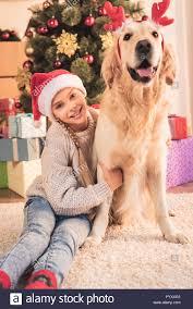Lächelnd Kind In Santa Hut Und Golden Retriever Hund Mit