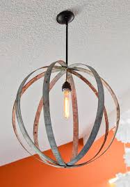 wine barrel rings were used to make a chandelier to hang on a vaulted ceiling a filament bulb was added to continue the antique feel