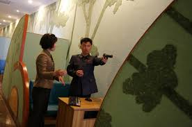 woos tourists a holiday in socialist fairyland a staff member coaches a n man at a shooting arcade