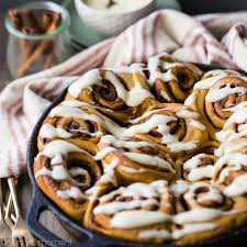 cast iron skillet with gingerbread cinnamon rolls drizzled with cream cheese icing cinnamon sticks