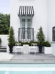 black and white greek key pool tile black and white striped awning and chairs and topiaries with matte black planters
