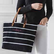woman holding monogrammed black striped canvas tote with custom embroidered script name