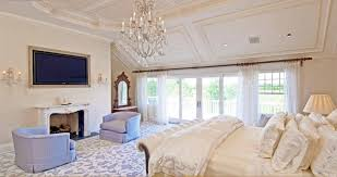 chic master bedroom with chandelier and ornate mirror also blue oversized chairs
