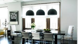 sleek modern kitchen with three black dome pendant lights hung over a black dining room table surrounded by upholstered chairs with higher b