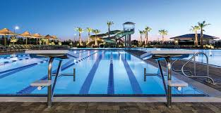 a view of the starting blocks lap pool and waterslides at dusk at the outdoor