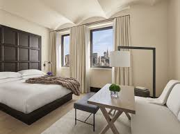 A Room With A King Bed, Two Windows Overlooking The City And A Seating Area