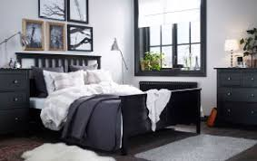 A large bedroom with a black-brown bed with bed textiles in beige/white