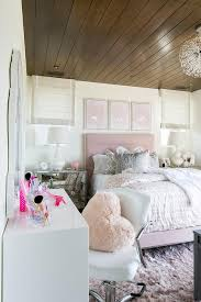 a faux fur heart shaped pillow sits on a white task chair positioned at a white lacquer dressing table placed beneath a jonathan adler queen anne mirror