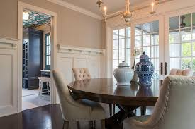 a classic dining room features white and beige hues with board and batten trim walls