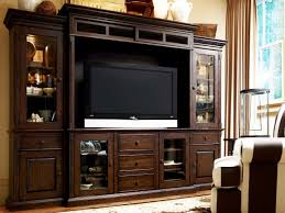dark brown wooden storage with tv on the middle of storage plus glass doors also drawers
