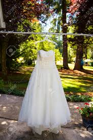 Wedding Dress With Lights White Wedding Dress Hanging Outdoors From Some Lights