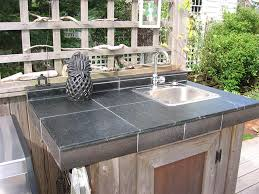 a vermont soapstone outdoor sink with both oiled and dry finish