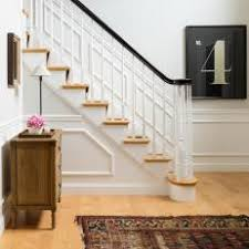 white foyer with chair rail and staircase with spindles