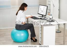 office exercise equipment. side view of pregnant businesswoman using computer while sitting on exercise ball in office equipment r