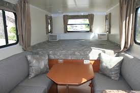An interior idea for mobile houses with large bedding grey sofa wooden  table and glass windows
