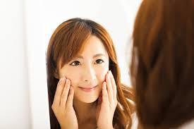 Dr Gregg Jantz Smiling Young Woman Looking Mirror In Bedroom