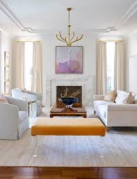 a greek key ceiling accented with a ruhlmann large chandelier illuminates a purple abstract art piece hanging over a marble art deco fireplace mantel