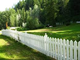white picket fence. A Picket Fence Serving As A Perimeter Of Graveyard In The Countryside. White