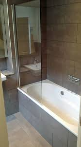 a small en suite bathroom with over bath shower and hinged bath screen designed and